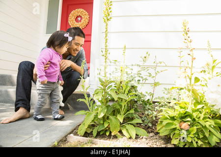 Mid adult man and toddler daughter looking at plants - Stock Photo