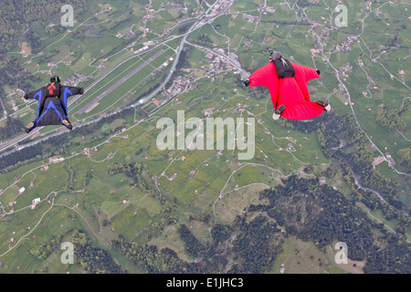 Two men flying above fields in wingsuits - Stock Photo