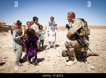 U.S. Army Staff Sgt. Matthew Parsons, assigned to Police Adviser Team Delaram, interacts with children in Delaram, - Stock Photo