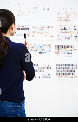 Young woman looking at photographs in studio - Stock Photo