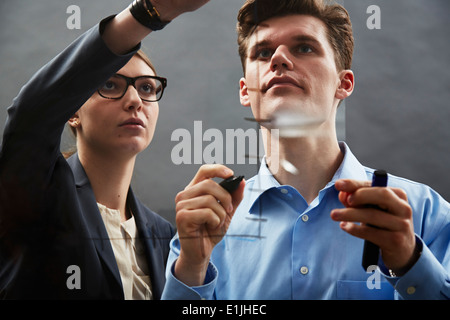 Business colleagues drawing graph on glass - Stock Photo