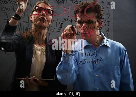 Business colleagues writing on glass - Stock Photo