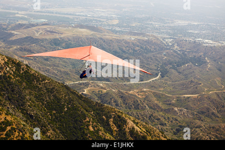 Man flying hang glider over valley - Stock Photo