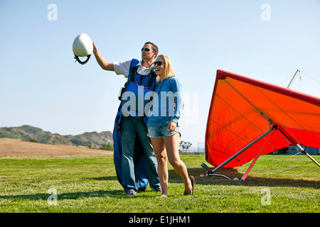 Couple enjoying view, hang glider in background