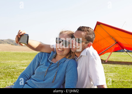 Couple taking selfie, hang glider in background - Stock Photo