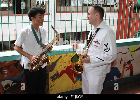A U.S. Sailor, right, with the U.S. 7th Fleet Band ensemble Orient Express explains breathing techniques for playing - Stock Photo