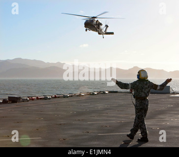 An Australian Army S70A-9 Black Hawk helicopter prepares to land on the flight deck of the Royal Australian Navy - Stock Photo