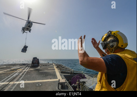 U.S. Navy Boatswain's Mate 2nd Class Rick Zuccaro signals a Military Sealift Command SA-330J Puma helicopter to - Stock Photo