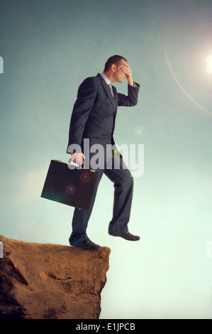 businessman with hands over eyes stepping off the edge of a cliff - Stock Photo