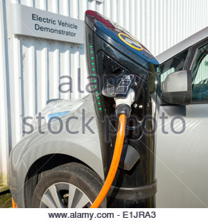 Electric car demonstrator on charge at a Nissan garage, UK - Stock Photo