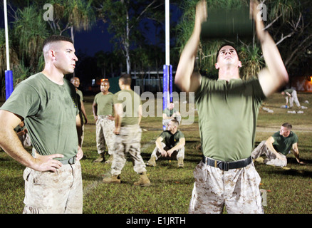 U.S. Marine Corps Staff Sgt. Daniel Hubbert, right, finishes the ammunition can lift portion of a combat fitness - Stock Photo