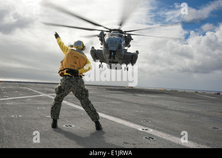 U.S. Navy Aviation Support Equipment Technician 3rd Class James Rockwell directs a Marine Corps CH-53E Super Stallion - Stock Photo