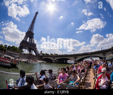 Tourists pass the Paris Eiffel Tower on a boat on the Seine river. - Stock Photo