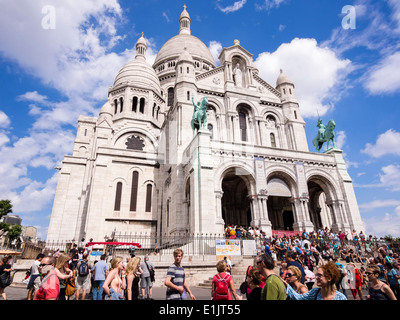 Tourists visit the Basilica of the Sacre Coeur on the Montmartre hill in Paris. - Stock Photo