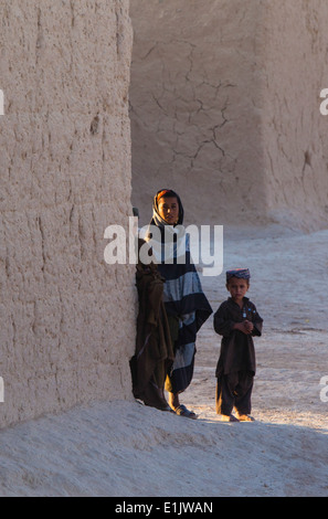 Afghan children watch a convoy of Marines pass their home during a combat logistics patrol conducted by Combat Logistics - Stock Photo