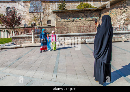 Mother taking picture of her sons in front of Mevlana museum - Stock Photo
