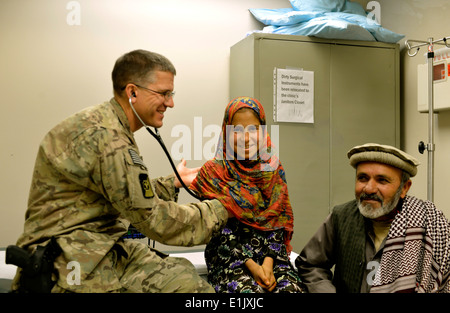 U.S. Air Force Lt. Col. David Jones, left, a pediatrician with the 455th Expeditionary Medical Group, examines an - Stock Photo