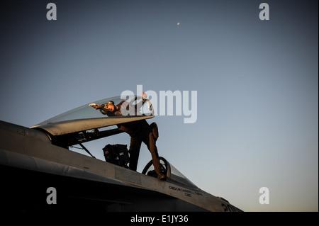U.S. Navy Aviation Structural Mechanic 3rd Class John Alden cleans the canopy of an F/A-18E Super Hornet aircraft - Stock Photo