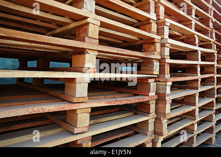 Wooden pallets stacked on top of each other in a timber yard - Stock Photo