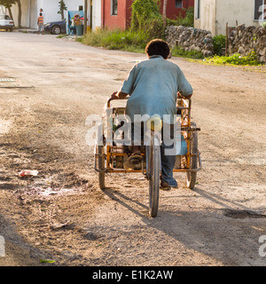 Going Home after work. A bicycle vendor shod in flip flops, dodges potholes on a back street in Tulum. - Stock Photo
