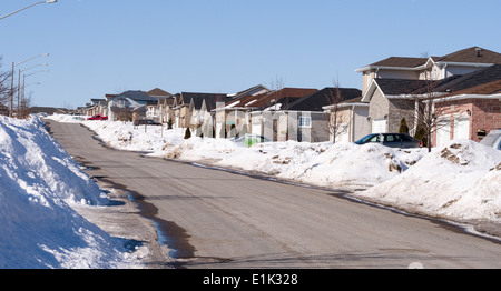 Suburban streetscape. A new subdivision during a snowy winter. Barren, uniform and sparse. Amherstview, Ontario, - Stock Photo
