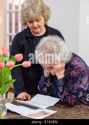 Reading a Letter. A senior woman reads a letter with her head in her hands while her daughter looks on. - Stock Photo