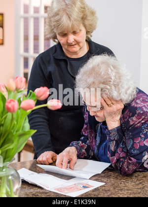 Reading the details of a Letter. A senior woman reads a letter, one hand following the text while the other supports - Stock Photo