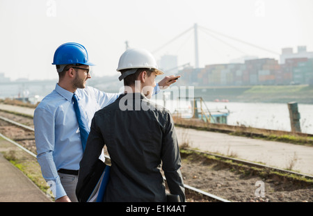 Businessman talking to teenager at container terminal - Stock Photo