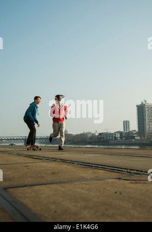 Young man and teenager jogging and skateboarding - Stock Photo
