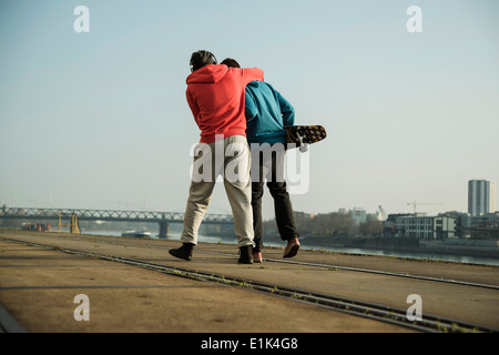 Young man and teenager with skateboard hugging - Stock Photo
