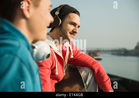 Young man and teenager with skateboard by the riverside - Stock Photo