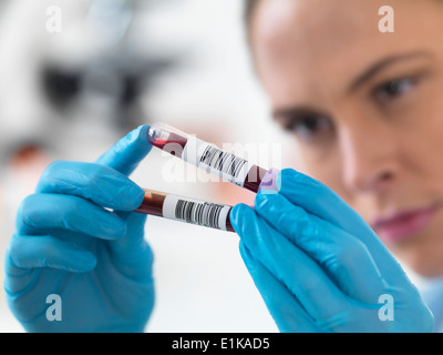 Female scientist holding blood samples in test tubes. - Stock Photo