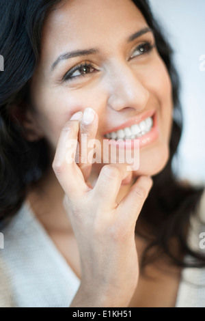 MODEL RELEASED Portrait of a woman with her fingers crossed. - Stock Photo