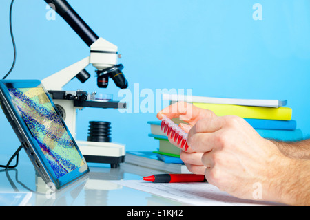 Laboratory technician holding microtubes with blood samples. - Stock Photo