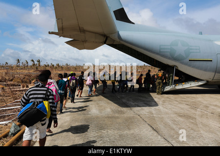 Philippine citizens affected by Typhoon Haiyan board a U.S. Marine Corps KC-130J Super Hercules aircraft in Guiuan, - Stock Photo