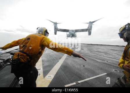 U.S. Navy Boatswain's Mate 3rd Class Brian Sherlock, a landing signalman enlisted, directs the first-ever landing - Stock Photo