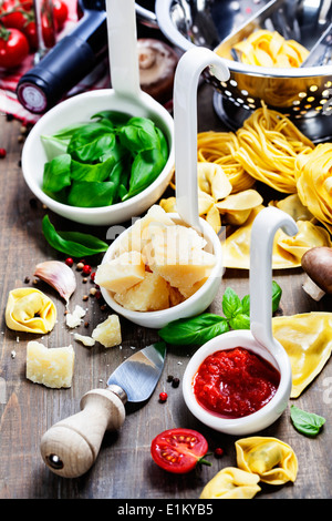 Fresh pasta and italian ingredients on wooden board - Stock Photo