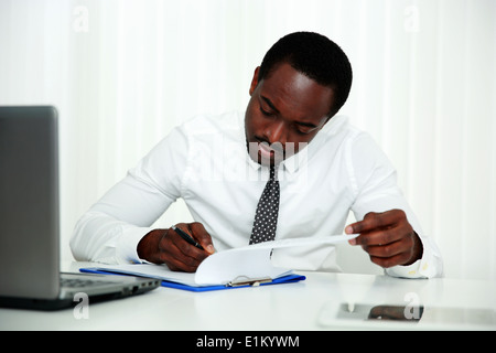 African man signing document in office - Stock Photo