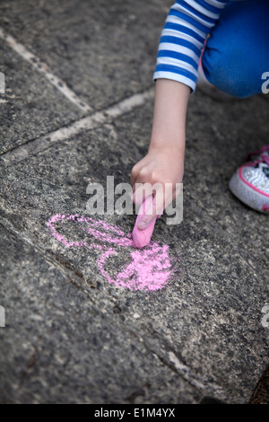Child drawing a pink chalk heart on a concrete sidewalk. - Stock Photo