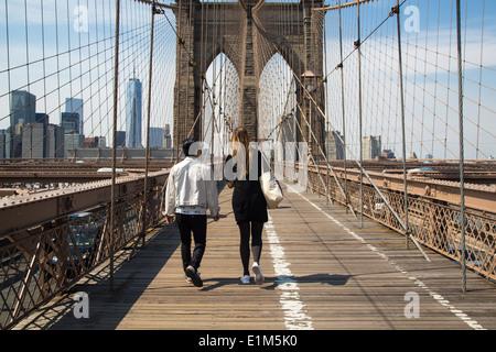 A Couple walking over Brooklyn Bridge - Stock Photo