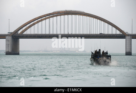 A U.S. Navy riverine command boat assigned to Commander, Task Group (CTG) 56.7 passes the Prince Khalifa Bin Salman - Stock Photo