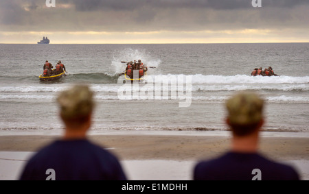 U.S. Navy SEAL candidates paddle inflatable boats into the incoming surf as their instructors look on during training - Stock Photo