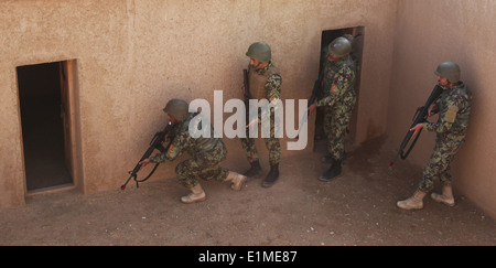 Afghan National Army soldiers with the 215th Corps enter a simulated enemy compound during a training course at - Stock Photo