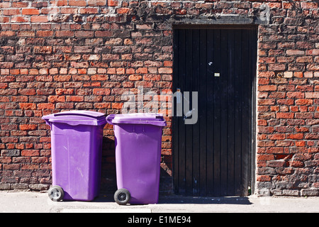 Wheelie bins against old brick wall - Stock Photo