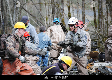 Rescue workers search for missing people March 26, 2014, in Oso, Wash. U.S. Service members with the Washington - Stock Photo
