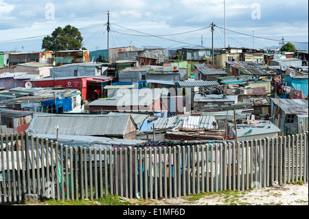 Corrugated iron sheds behind a fence in Khayelitsha, Cape Town, South Africa - Stock Photo