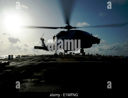 A Greek navy MH-60R Seahawk helicopter assigned to the Greek frigate HS Salamis (F 455) prepares to land on the - Stock Photo