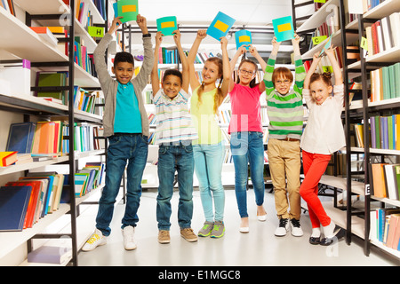 Six children with hands up hold exercise books - Stock Photo