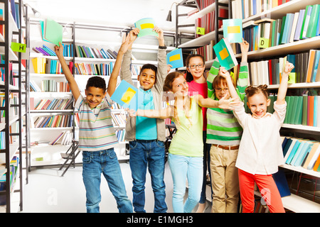 Happy children with hands up hold exercise books - Stock Photo