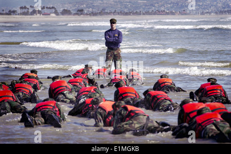 US Navy SEAL candidates during Hell Week surf drill part of the Basic Underwater Demolition/SEAL conditioning program - Stock Photo